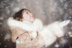 A cute little girl in a fur coat enjoys the falling snow Stock Photos