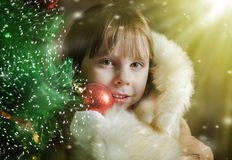 A cute little girl in a fur coat near the Christmas tree Stock Photo