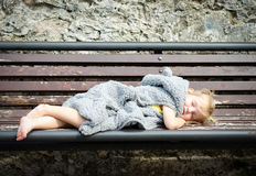 Cute little girl in fur coat sleeping on the bench in park Royalty Free Stock Photo