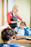 Cute little girl getting her new haircut. In a barbershop Stock Images