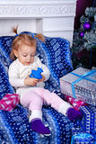 Cute little girl and gifts near Christmas tree. Stock Photography