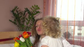 Cute little girl give flowers to happy mom and kiss on mother day stock video footage