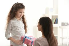 Cute little girl giving gift box to her mom. Indoors. Mother`s day celebration Stock Photos