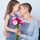 Cute little girl giving mom bouquet of pink gerbera daisies. Loving mother and daughter smiling and hugging. Happy Mother`s Day, Women`s day or Birthday Royalty Free Stock Photography