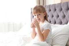 Cute little girl with glass of fresh water sitting in bed at home. Space for text royalty free stock image