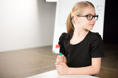 Cute little girl in glasses. With marker near presentation board Royalty Free Stock Photos