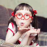 Cute little girl with glasses in the shape of a Stock Photo