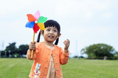 Cute little girl on grass in summer day holds windmill Stock Image