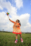 Cute little girl on grass in summer day holds windmill Royalty Free Stock Photos