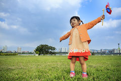 Cute little girl on grass in summer day holds windmill Stock Photo