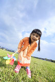Cute little girl on grass in summer day holds windmill Royalty Free Stock Photo