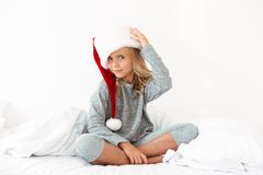 Cute little girl in gray pajamas touching her fluffy Santa`s hat Royalty Free Stock Photos