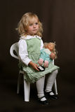 Cute little girl in green dress with doll. Little girl seating Royalty Free Stock Images