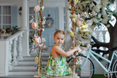 Cute little girl in a green dress sitting on swings decorated wi Stock Photography