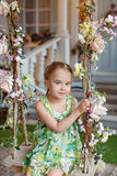 Cute little girl in a green dress sitting on swings decorated wi Stock Photos
