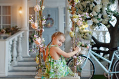 Cute little girl in a green dress sitting on swings decorated wi. Th flowers on the background of the house and smiling royalty free stock image