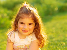 Cute little girl on green field Royalty Free Stock Image