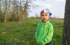 Cute little girl in green on the meadow in spring day Stock Images