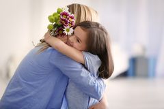 Cute little girl greeting her mother at home Stock Photos