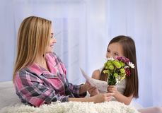 Cute little girl greeting her mother at home. Stock Image
