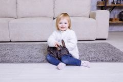Cute little girl with grey Easter rabbit, bunny. Blonde baby girl smiling in white sweater and blue jeans sitting at home on the c Stock Images