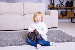 Cute little girl with grey Easter rabbit, bunny. Blonde baby girl smiling in white sweater and blue jeans sitting at home on the c Royalty Free Stock Photos