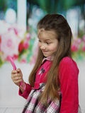 Cute little girl grimaces and looks in mirror Royalty Free Stock Photo