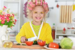 Cute little girl with hair curlers cooking at kitchen stock image