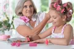 Little girl   with granny with magazine and nail polish. Cute little girl in  hair curlers  with granny beautifying themselves Stock Photos