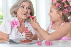 Little girl   with granny with magazine and nail polish. Cute little girl in  hair curlers  with granny beautifying themselves Stock Photo