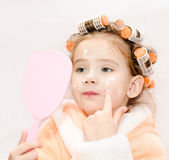 Cute little girl in hair curlers with mirror applying cream  Stock Images