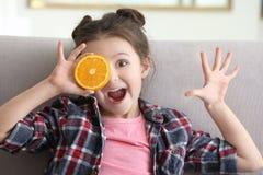 Cute little girl with half of orange sitting on sofa stock photo