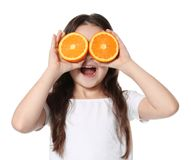 Cute little girl with halves of orange. On white background stock images