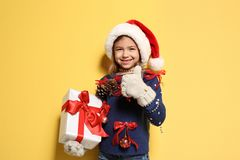 Cute little girl in handmade Christmas sweater and hat holding gift. On color background royalty free stock image