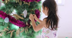 Cute little girl hanging ornament on Christmas tree stock video