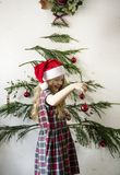 Cute little girl hanging up Christmas ornaments Stock Photos