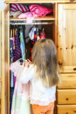 Cute little girl hanging up her clothes. Into the wardrobe Stock Photography