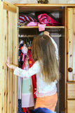 Cute little girl hanging up her clothes. Into the wardrobe Stock Photos