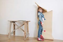 Cute little girl hanging wallpaper Stock Photos