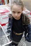Cute little girl happy with shopping cart. Royalty Free Stock Images