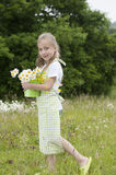 Cute little girl harvesting flowers. In a bucket Royalty Free Stock Photography