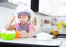 Cute little girl in apron whisking eggs Stock Photo