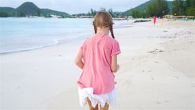 Adorable little girl running on the beach. Happy kid enjoy summer vacation. Slow Motion. Cute little girl in hat at beach during caribbean vacation stock video