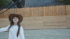 Cute little girl in hat comes and caresses black mare`s head stock video