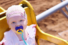 Cute little girl in hat with pacifier riding on carousel royalty free stock photo