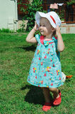 little girl with hat posing on the garden grass Royalty Free Stock Photo