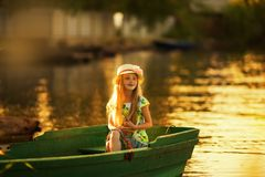 Cute little girl in a hat sitting in a boat on a lake at sunset Stock Photo