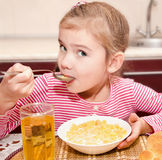 Cute little girl having breakfast cereals with milk and juice Stock Images