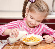 Cute little girl having breakfast cereals with milk Stock Images