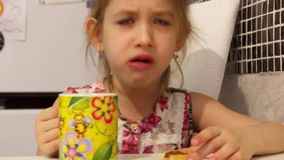 Cute little girl is having a breakfast. Child eating cookies and drinking tea. stock video